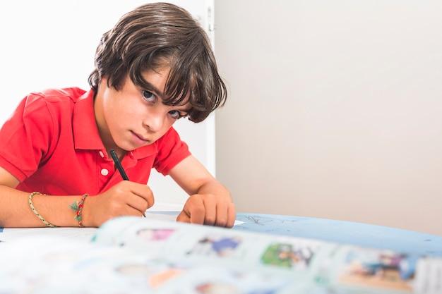 Petit garçon dessin assis à table