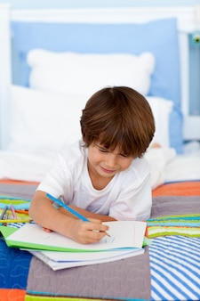 Petit garçon dessin au lit