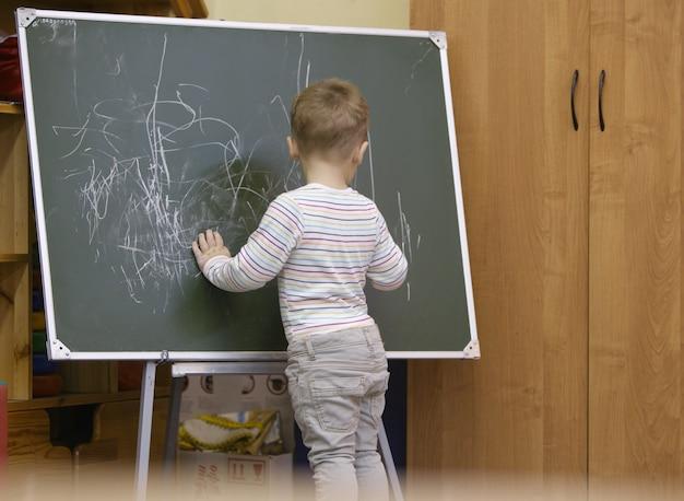 Petit garçon dessin sur un tableau au jardin d'enfants