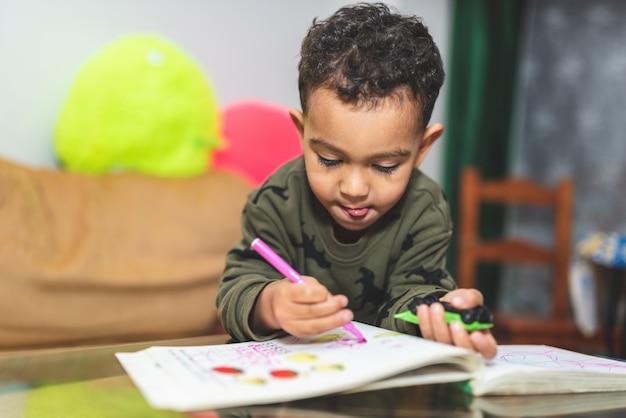 Petit garçon dessinant sur un cahier