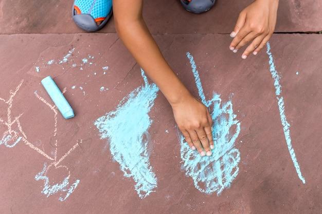 Petit garçon dessinant avec la craie de couleur sur le plancher de brique