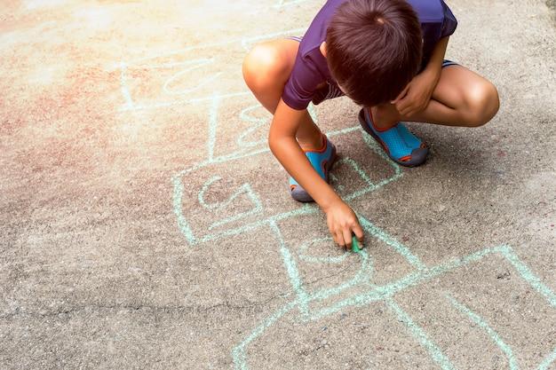 Petit garçon dessinant avec la craie de couleur sur le sol de la rue