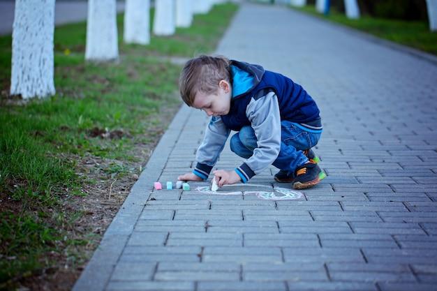 Petit garçon dessine sur l'asphalte dans le parc du printemps.