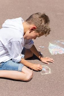 Le petit garçon dessine avec une craie sur un trottoir