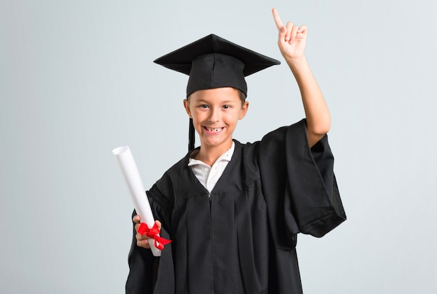 Petit garçon diplômé debout et pense à une idée sur fond gris