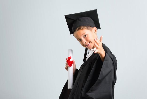 Petit garçon diplômé handshaking après une bonne affaire sur fond gris