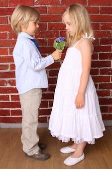 Petit garçon donne à une fille un beau bouquet de fleurs.