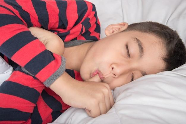 Petit garçon dort avec le pouce dans la bouche