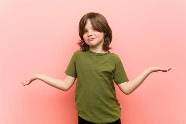Petit garçon doutant et haussant les épaules en questionnant le geste.