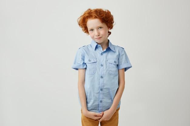Petit garçon drôle avec des cheveux bouclés rouges et des taches de rousseur se tenant la main, se sentant coupable