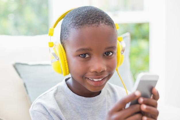 Petit garçon en écoutant de la musique sur le canapé