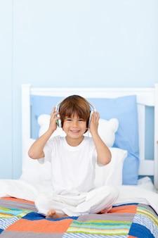 Petit garçon écoutant de la musique dans son lit