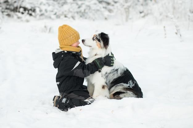 Petit garçon embrassant le berger australien dans la forêt d'hiver.