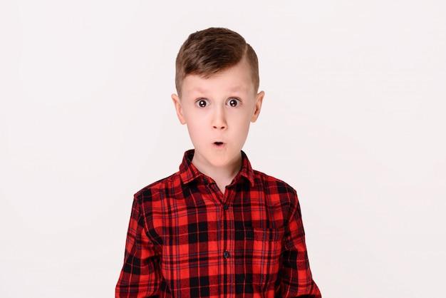 Le petit garçon avec une émotion expressive sur fond blanc.