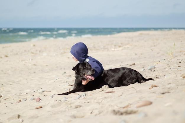 Petit garçon (enfant) avec chien noir au bord de la mer, concept d'amitié