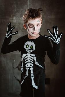 Petit garçon enfant en costume de squelette au carnaval d'halloween dans un paysage impressionnant