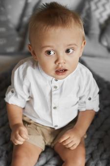 Petit garçon enfant dans une chemise blanche et un short beige souriant et regardant de côté alors qu'il était assis