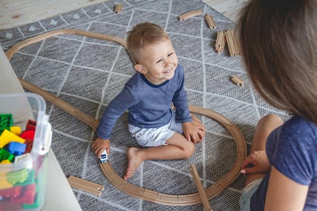 Petit garçon enfant et sa mère jouant avec le chemin de fer assis sur le sol
