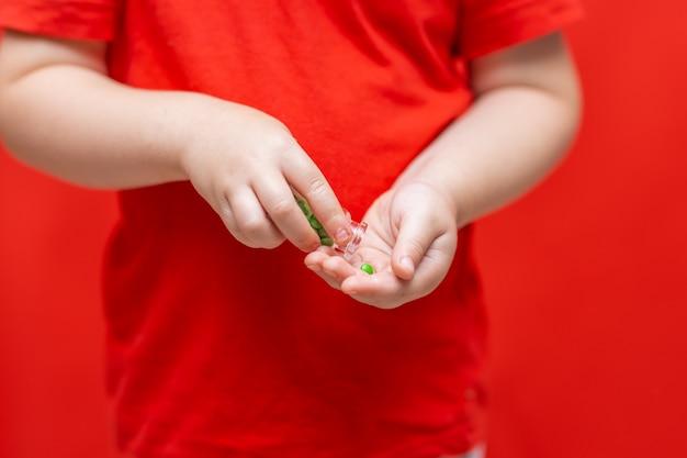 Petit garçon enfant verse des pilules de la canette dans la main
