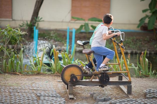 Petit garçon, équitation, vélo puissance, gymnase, à, cour de récréation