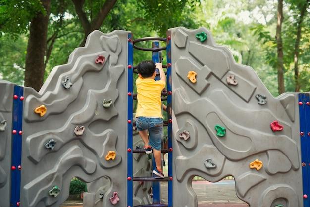 Petit garçon escalade échelle sur aire de jeux