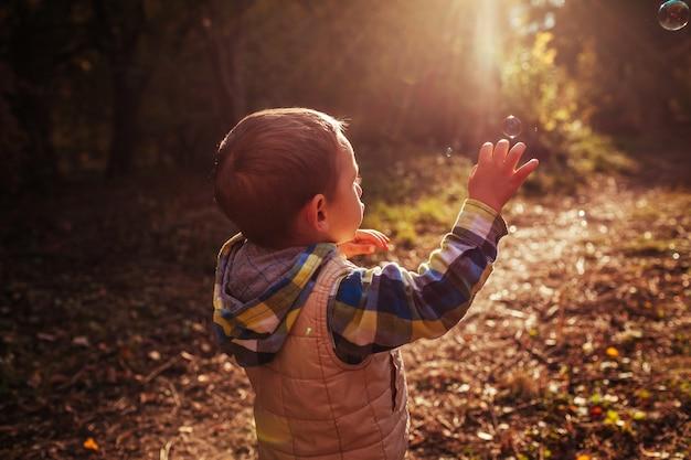 Petit garçon essayant d'attraper des bulles dans la forêt d'automne