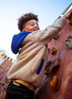 Petit garçon essayant un mur d'escalade