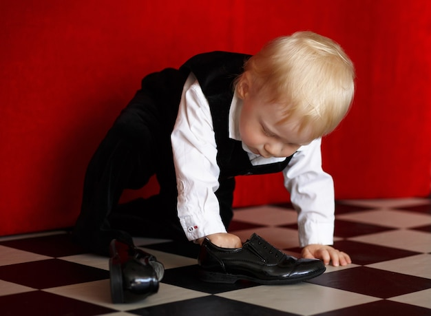 Petit garçon essayant de porter des chaussures en cuir verni