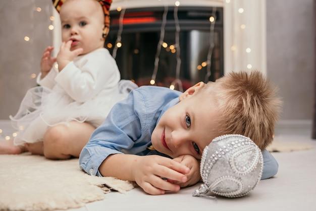 Un petit garçon est allongé sur un tapis de fourrure allongé avec un bal du nouvel an