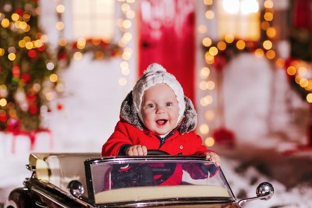 Petit garçon est assis dans un cabriolet pour enfants rouge