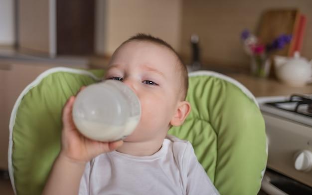 Petit garçon est assis dans une chaise d'alimentation et boit dans une bouteille