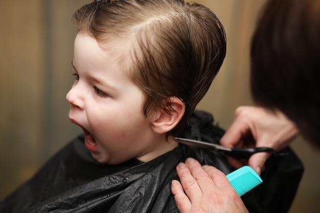Un petit garçon est taillé dans les émotions vives du coiffeur sur son visage