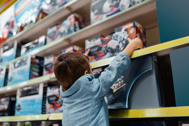 Petit garçon à l'étagère dans le magasin pour enfants, vue latérale