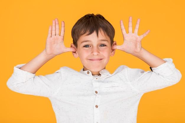 Petit garçon étant idiot avec un fond orange