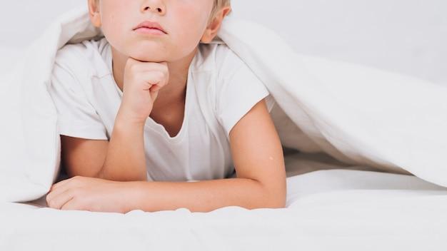 Petit garçon être sérieux dans lit