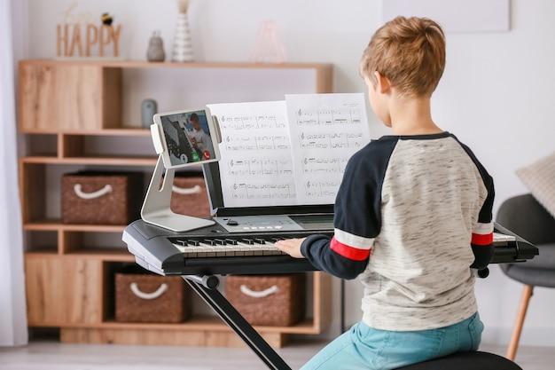 Petit garçon étudiant la musique avec son ami en ligne à la maison