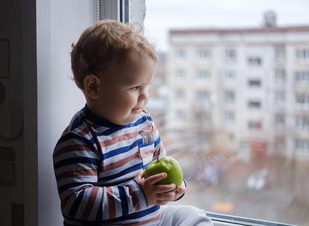 Petit garçon européen mange une pomme verte assise sur le rebord de la fenêtre dans la chambre