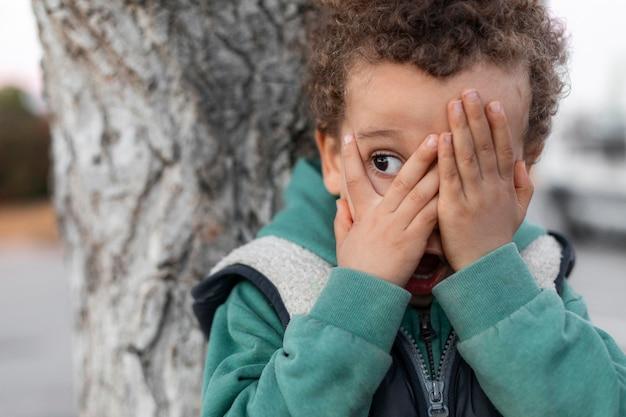 Petit garçon à l'extérieur couvrant son visage