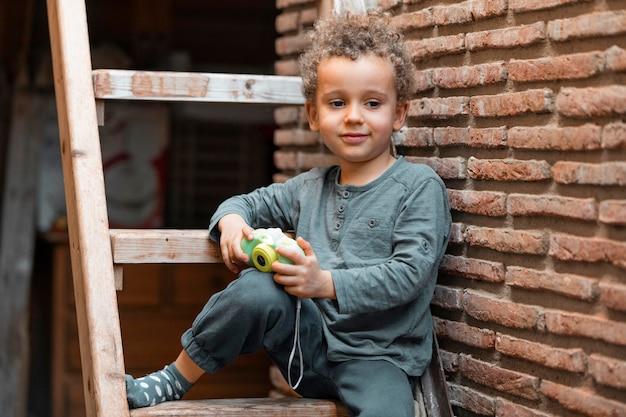 Petit garçon à l'extérieur avec jouet appareil photo