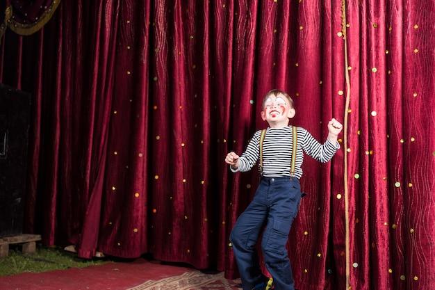 Petit garçon exubérant se produisant sur scène lors d'une pantomime debout devant les rideaux bordeaux fermés faisant son acte dans son costume et son maquillage avec un sourire riant, avec fond