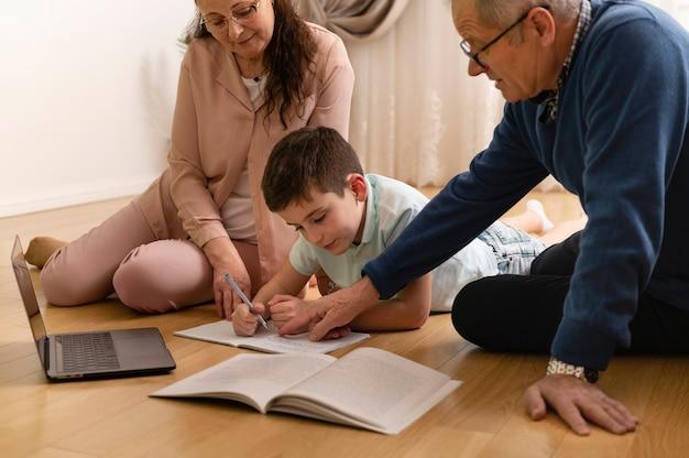 Petit garçon à faire ses devoirs avec ses grands-parents à la maison