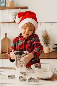 Petit garçon faisant un biscuit de noël