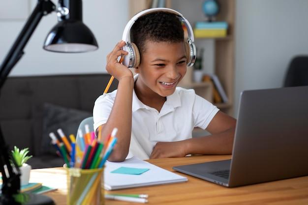 Petit garçon faisant l'école en ligne
