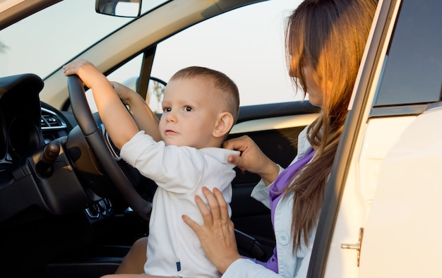 Petit garçon faisant semblant de conduire avec ses mains sur le volant alors qu'il était assis sur les genoux de sa mère