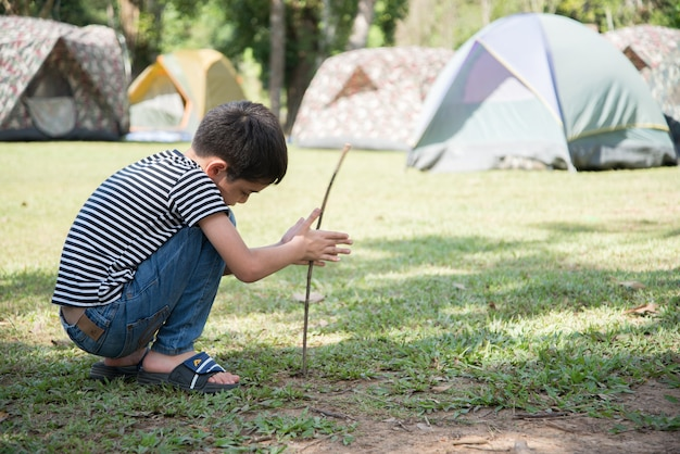 Petit garçon faisant une tente de camp activité d'été en plein air avec la famille