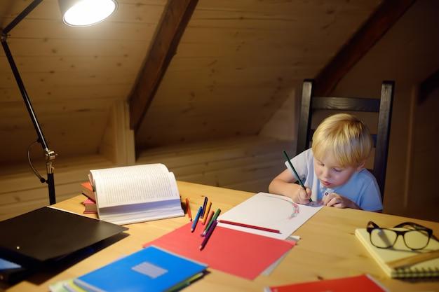 Petit garçon fait ses devoirs, peinture et écriture au soir à la maison. les enfants d'âge préscolaire apprennent des leçons - dessiner et colorier des images entraînement des enfants à écrire et à lire.