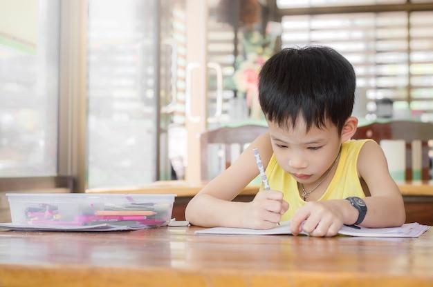 Petit garçon fait ses devoirs pour l'école sur le bureau à la maison
