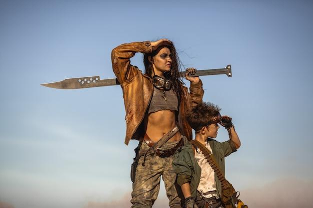 Petit garçon et femme en costumes post-apocalyptiques