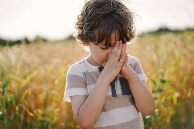 Le petit garçon ferma les yeux, priant dans un champ de blé. les mains jointes en prière. photo de haute qualité