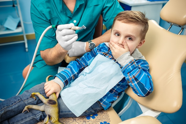 Un petit garçon ferme une bouche une paume. au cabinet dentaire